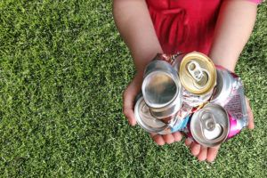Recyclable cans in child's hands